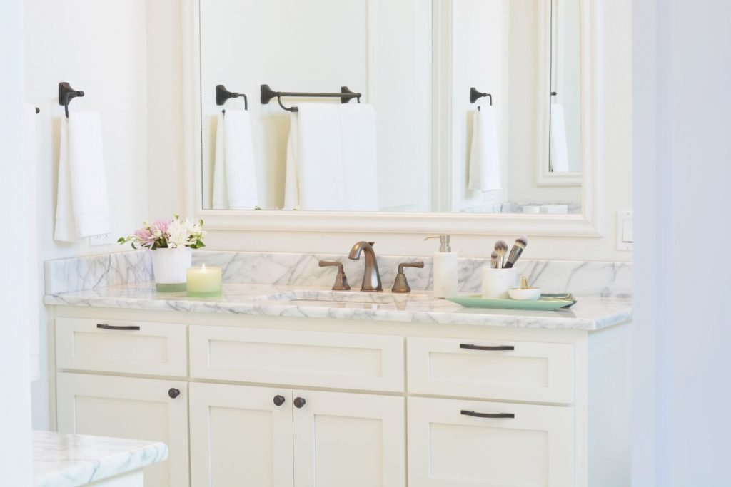 Durable vanity with gorgeous countertop and simple fixtures for a balanced and budget-friendly bathroom look.