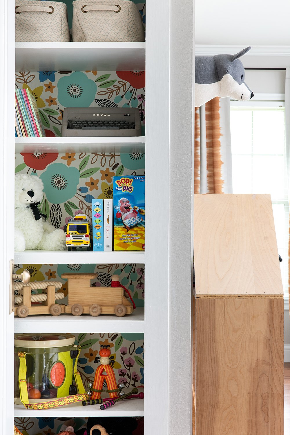 A built-in bookshelf with wallpaper by interior designer Lesley Myrick