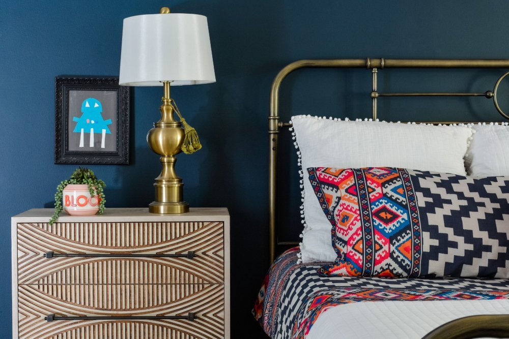 A carved wooden nightstand and colorful bedding in a navy master bedroom by interior designer Lesley Myrick