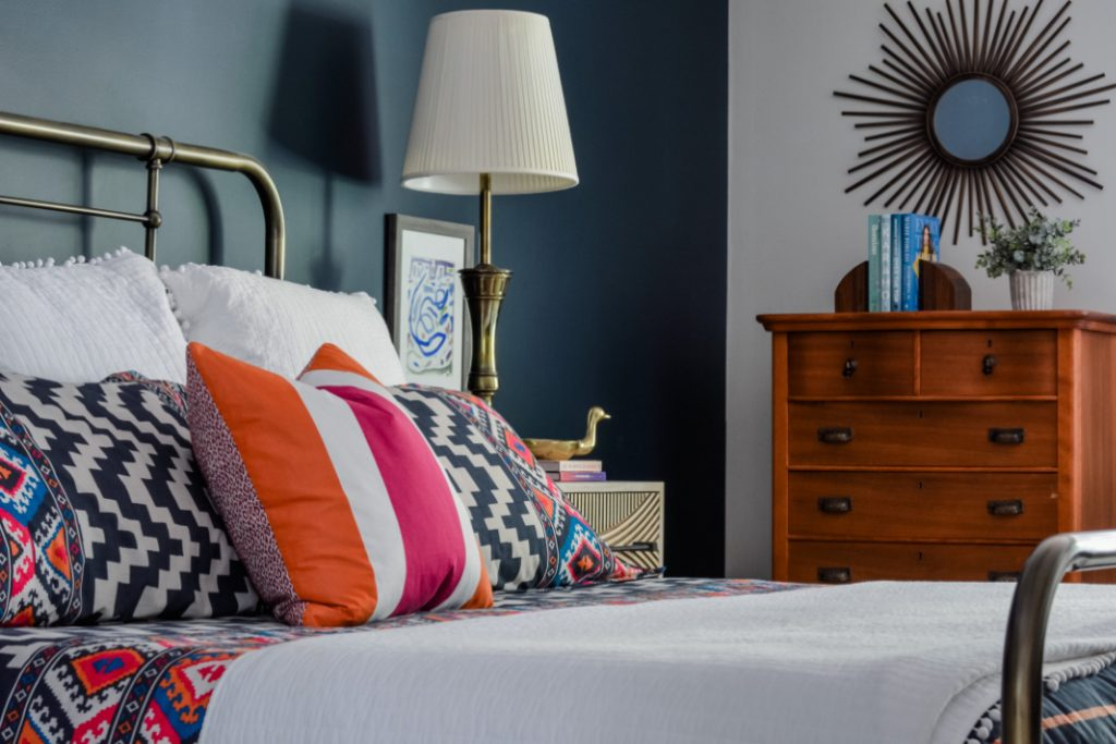 Hot pink and orange bedding in a navy master bedroom by interior designer Lesley Myrick